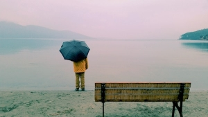 Person holding umbrella at misty lakeshore